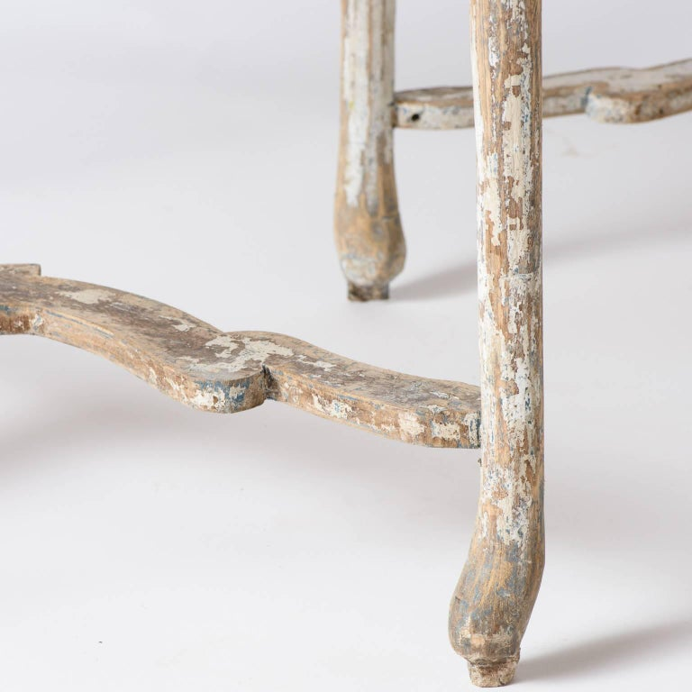 These demilune tables have the beautiful well-worn look only found on treasured pieces of furniture handed down over time. They have great form with curved legs and unique stretchers showing traces of old white paint. The scrubbed tops have a lovely