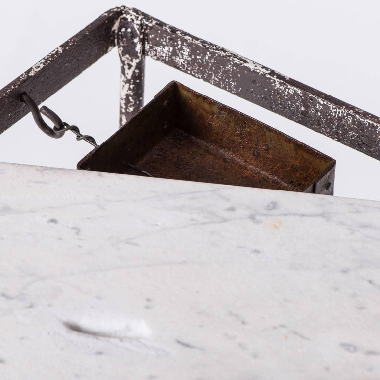 This elegant table is somewhat unusual in that it has a slot carved in the marble top with an attached cash box underneath which could have been to leave tips in a restaurant, or coins for some kind of game. The base has a graceful design with