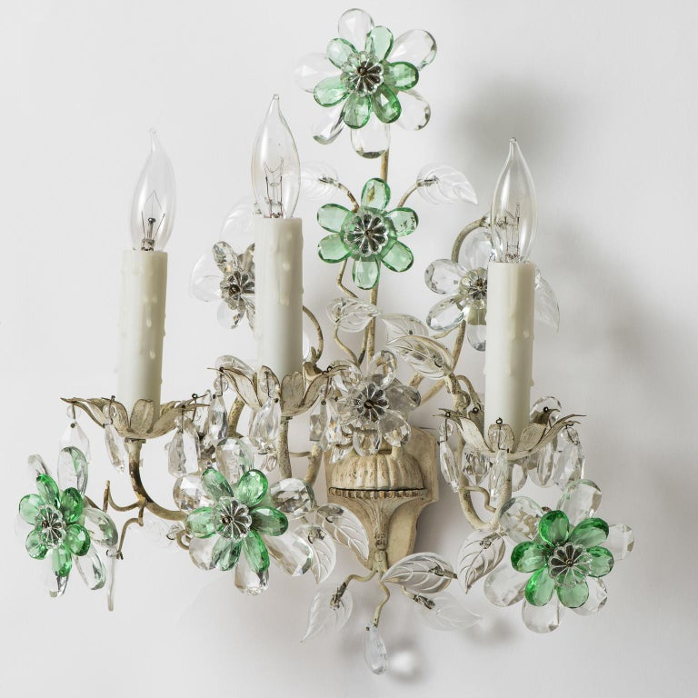 These charming three-light sconces featuring a white painted metal center urn and three arms ending in crystal flowers. The crystals are an unusual combination of clear and pale green giving them a light and airy feel. They have been recently