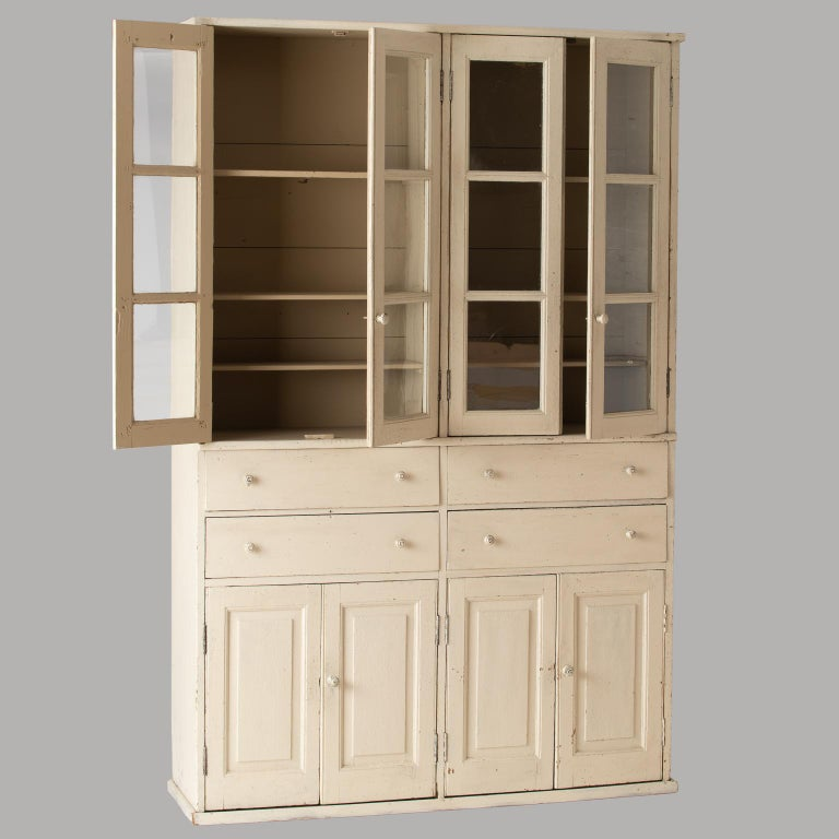This useful cupboard has the look of a piece that might have been the focal point of a country kitchen in Provence. With glass doors and three interior shelves, it is ideal for displaying glasses, and the four centre drawers are the perfect spot for