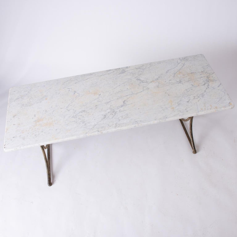 This table has a wonderful antique white marble top that is almost one inch thick. The base, made of handwrought iron, has a very sleek and unusual design with a surface that shows traces of old bronze paint. The marble top shows some discolorations