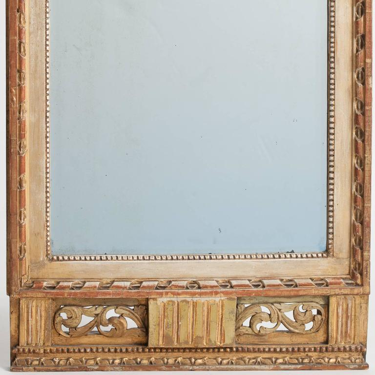 This elegant mirror was made in Stockholm, circa 1780 and bears the official stamp of the Stockholm mirror guild as well as the personal stamp of the maker and certified gilder, Lago Lunden (1744-1819). The mirror has a lovely gilded bow and