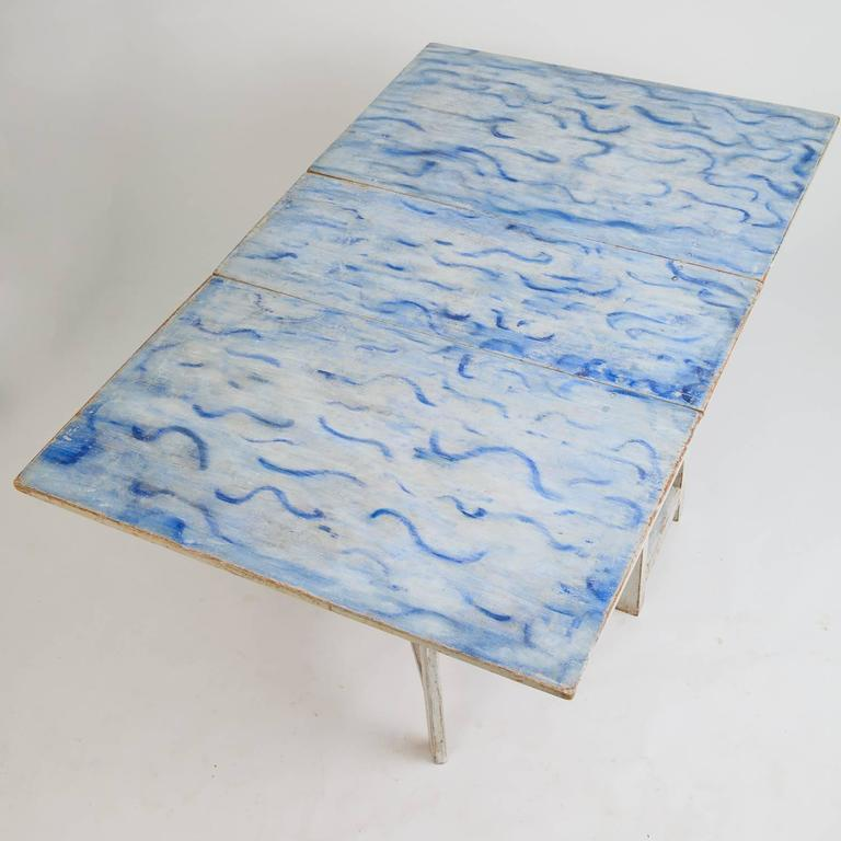 This fantastic Swedish drop-leaf table (slagbord) is a once in a lifetime piece with a beautiful original painted top surface with vibrant waves of blue against a white background. The base retains the original white paint and the leaves drop down