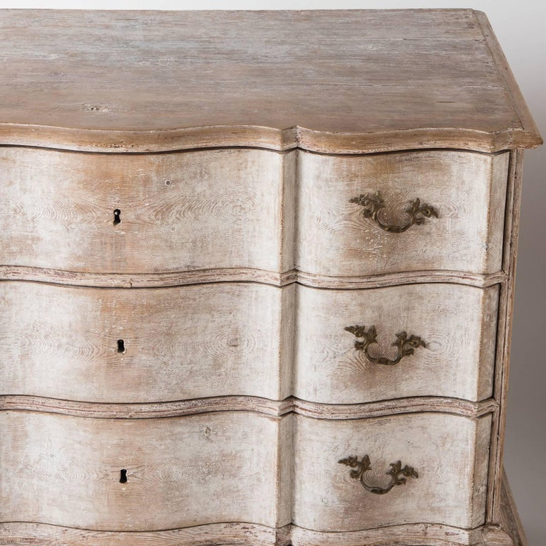 This important three drawer chest with a graceful serpentine front sits on a separate base with slightly exaggerated curved legs which adds to it stature. The paint surface with touches of white paint remaining is all original. The hardware is