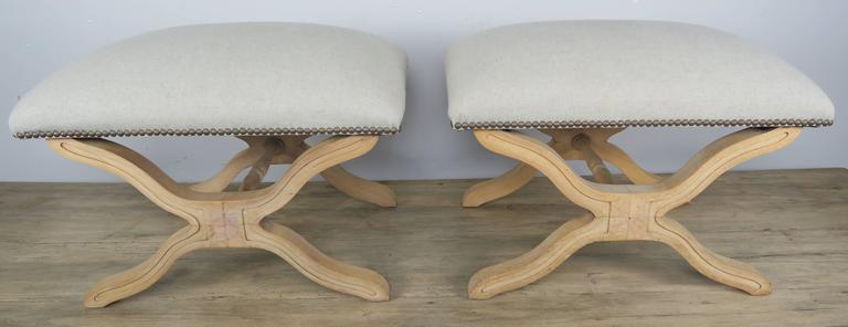 "Pair of Swedish ""X"" benches in a natural wood finish newly upholstered in Belgium linen with nailhead trim detail."