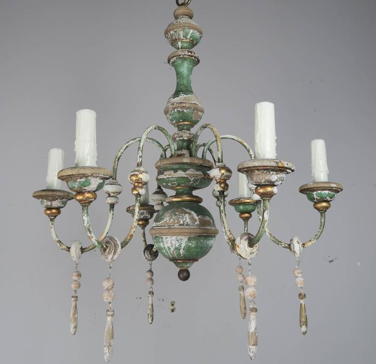 "Six-light Italian painted and parcel-gilt chandelier with wood tassel drops. The fixture has been newly rewired with drip wax candle covers. Includes 36"" of chain and canopy."