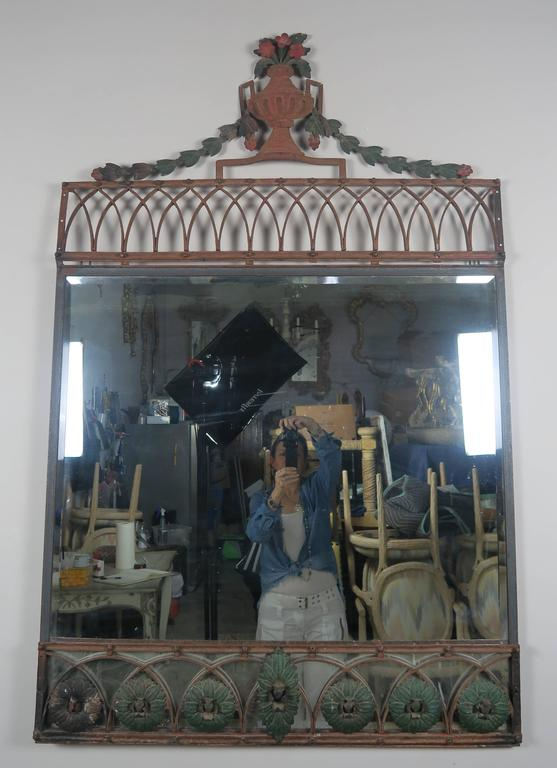 Painted French wrought iron mirror with centre top urn and rosettes across the bottom. Newer mirror inset with 1