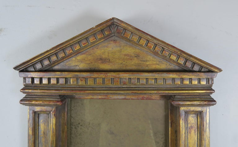 19th century Italian neoclassical style carved giltwood mirror in the shape of a portico. Aged smokey mirror from year of exposure. Distressed finish with missing gilt throughout.