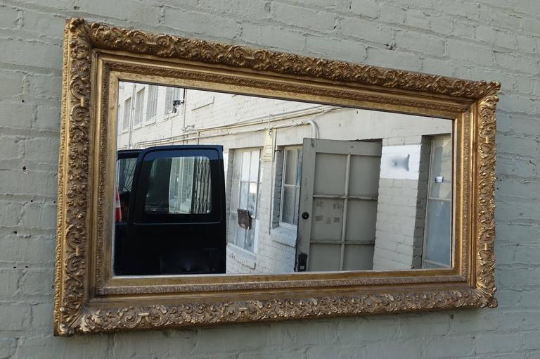 19th century carved Italian giltwood mirror with intricate carved details throughout.