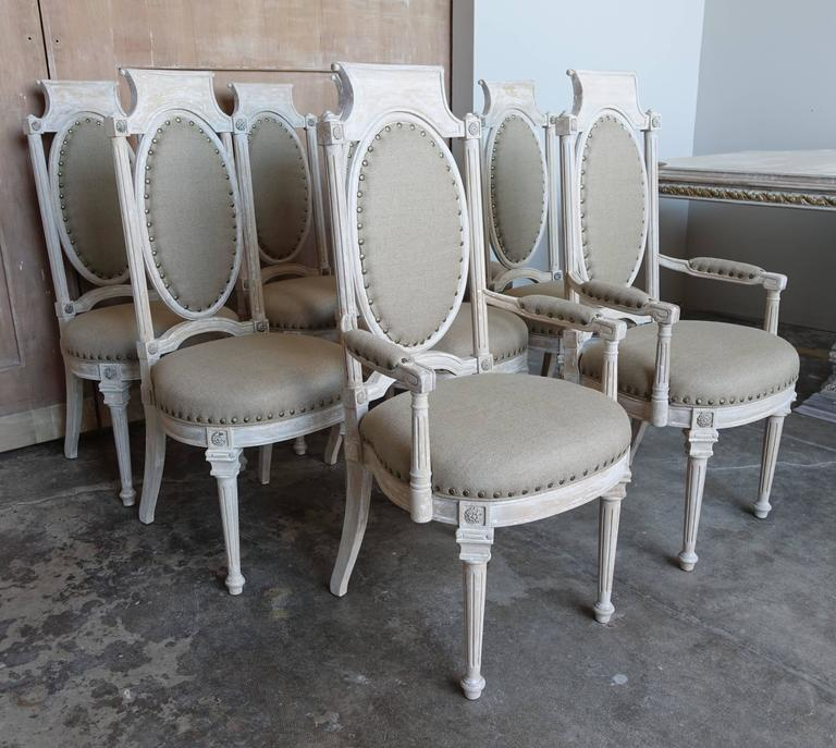 Set of eight Italian painted neoclassical style dining chairs newly upholstered in Belgium linen with floral nailhead trim detail.