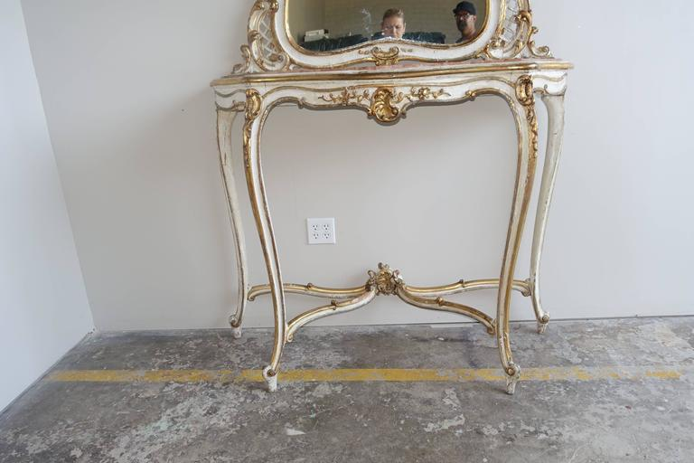 Louis XVI style painted and parcel-gilt console and mirror with original marble top. Console stands on four elegant cabriole legs with rams head feet. Bottom stretcher meets at center finial. Acanthus leaf detailing in 22-karat gold leaf finish.
