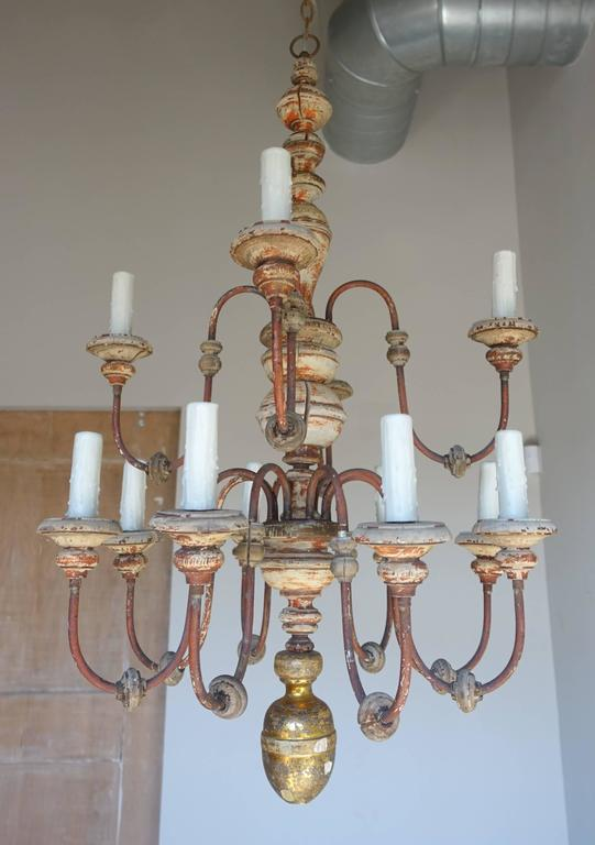 Twelve-light two-tiered Italian wood and iron painted and parcel-gilt chandelier. Newly rewired with drip wax candle covers. Includes chain and canopy.