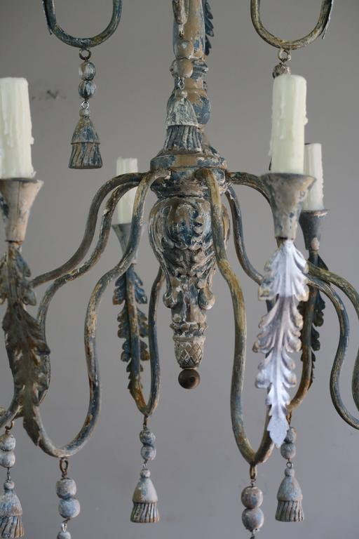 Twelve-light Italian iron and wood painted chandelier with tassels and acanthus leaves throughout. Newly rewired with drip wax candle covers. Ready to install and includes chain and canopy. A pair is available if needed.