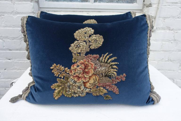 Pair of custom pillows made with 19th century French metallic and chenille handmade embroidered textiles hand applied on contemporary deep blue velvet and finished with handmade tassel fringe at both sides. Down inserts. Sewn shut.