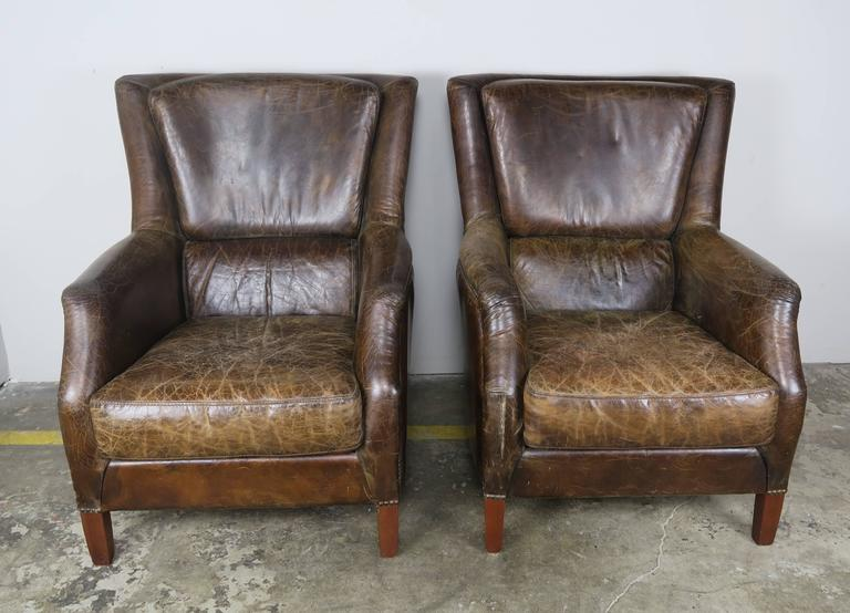 Pair of French deco style tobacco colored leather upholstered armchairs with loose seat cushions and nailhead trim detail. The armchairs stand on four walnut straight tapered legs.