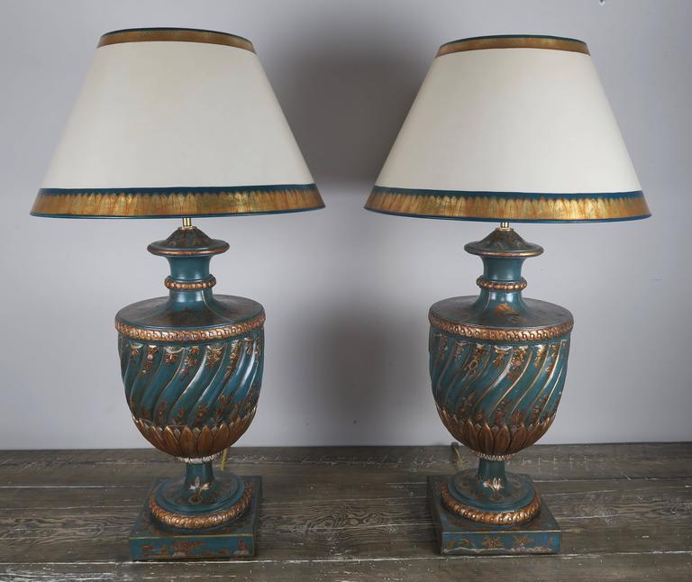 Pair of teal and raised gold chinoiserie decorated urn lamps that have been crowned with hand-painted parchment shades. The lamps are newly wired and are in working condition with two standard sockets each lamp.    Shade size: 10