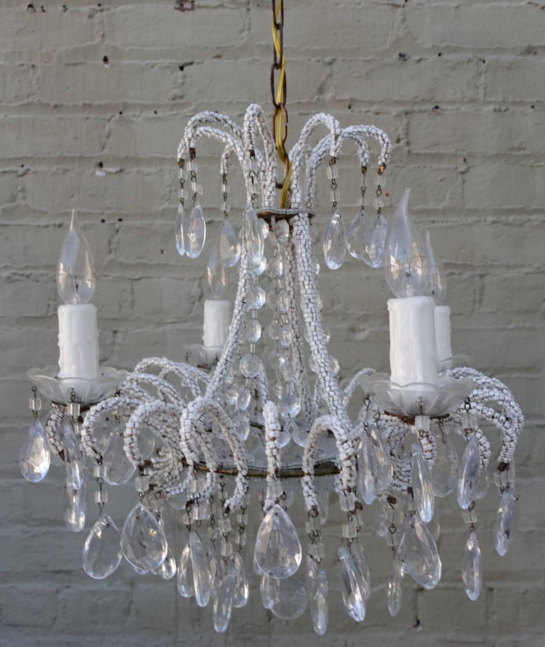 Crystal waterfall style chandelier with tiny white beads strung finely around the arms and almond shaped crystals combined with macaroni beads can be seen throughout. The fixture has been newly rewired with drip wax candle covers and crystal cups.