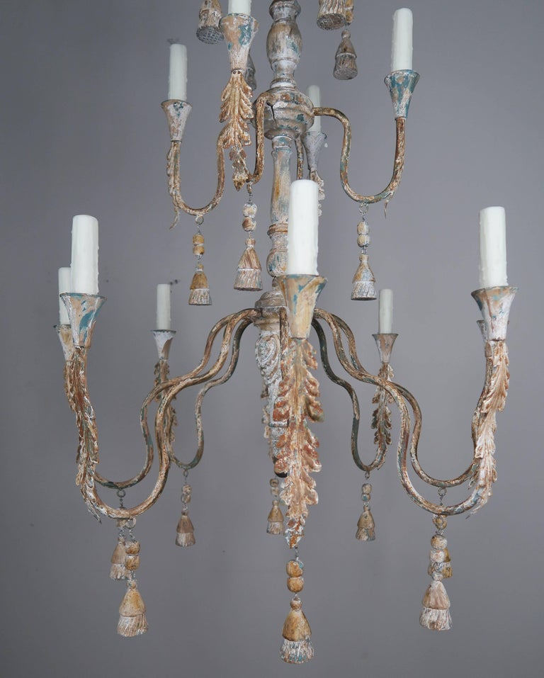 Offered by Melissa Levinson Antiques  Pair of two-tiered Italian painted chandeliers with carved wood tassels and beads throughout. The paint on the fixtures is beautifully worn with an antique cream base and remnants of blue paint, rust and natural