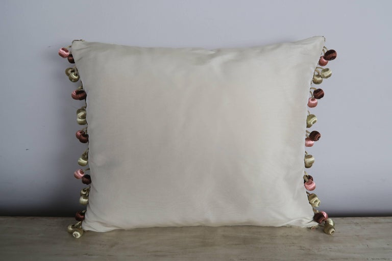 Pair of custom pillows made with 19th century French metallic and chenille embroideries applied to contemporary linen velvet and finished with a multi colored ball fringe detail. Down inserts, zipper closures.