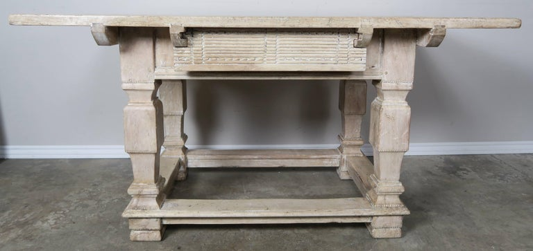Pair of Italian Baroque style walnut carved primitive rectangular shaped tables with center drawers. The table stand on four straight legs that are connected by a stretcher.