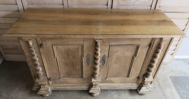 18th century Italian Baroque style bleached walnut credenza with twisted barley detail flanking both doors. The piece stands on six large bun feet. Original hand forged metal hardware and key. Interior is painted.