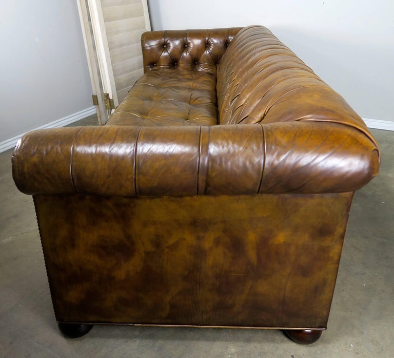 Rich Brown English Tufted Leather Chesterfield Style Sofa Standing On Six Ebonized Bun Feet And Finished