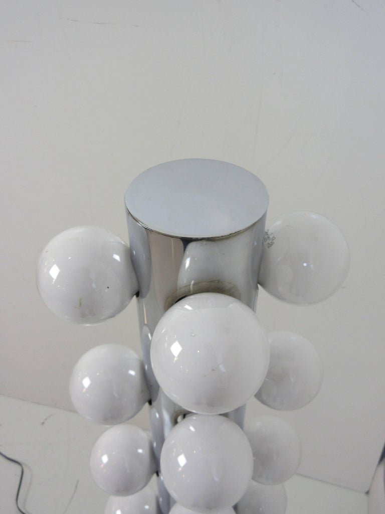 Robert Sonneman floor lamp in chrome with 16 vanity light bulbs on dimmer for infinite possible lighting intensities. This lamp was part of a series of lamps with matching table lamps. Tall cylinder on disk base rises four feet with bulbs on the top