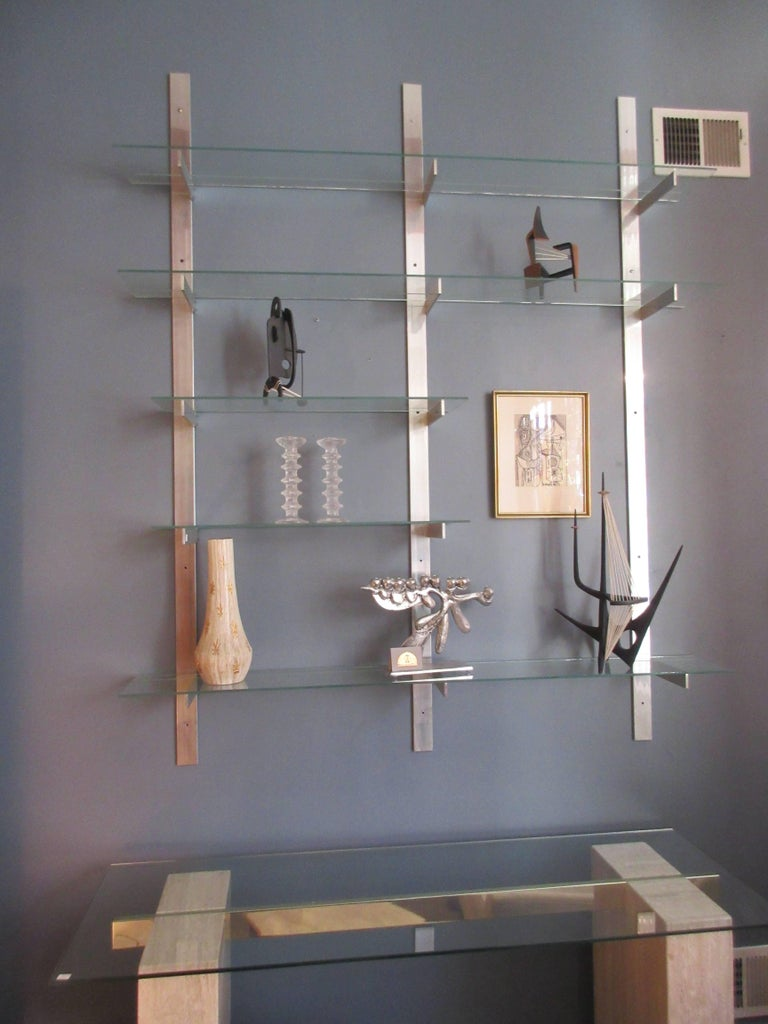 Aluminium and glass shelving unit in the style of pace. Three aluminium pieces screwed directly into the wall support five shelves. All placements of the shelves are adjustable in placement. Measures: Three shelves are 60 inches and two are 30.