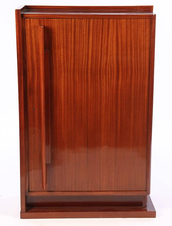 French Art Deco modernist cabinet by Andre Sornay in African mahogany. Detailed with storage shelving interior. Measures: 32