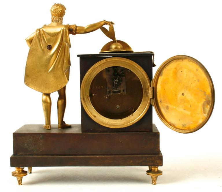 This handsome bronze mantel clock is from the French Empire period with a standing figure placing his feathered hat on top of the clock. The clock's enameled face is surrounded by an ormolu twisted rope frame. The base is mounted with a tournament