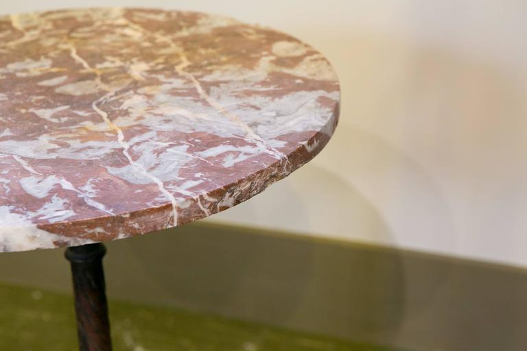 Beautiful antique French gueridon table with decorative iron base and Rouge Griotte red and white marbled top. This type of marble is indigenous to France. Wonderfully detailed casting on the base. Would make a great bedside table.