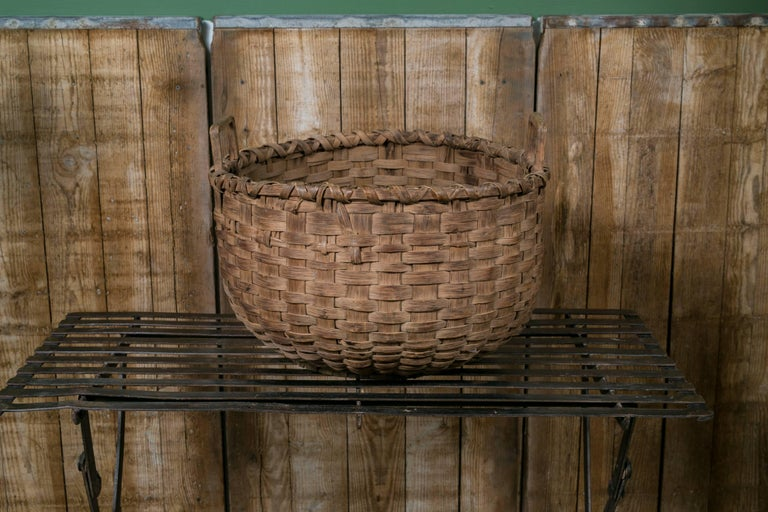 Handcrafted antique American-made hardwood splint basket. Two woods handles on top in a rectangular shape. Large in size, see measurements below. Height is to the top of the handles.