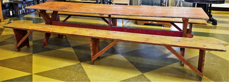 Charming, rustic trestle-base table with X-frame. Comes with two matching plank benches. Over-painted in red. From Sweden, circa 1780-1820. Decorative support bases on the benches and table. Very long and unusual in its size. Price is for table and