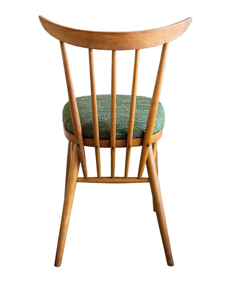 Set of four 1950s French dining chairs with upholstered seat and spindle back.