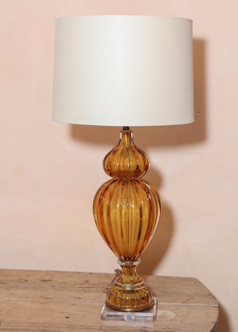 Murano amber color glass lamp by Masbro. Mid-Century Modern blown glass lamp made for Marbro Lamp Company, circa 1960. Updated with Lucite base and a complementary linen shade (measurements include shade). Newly wired for use within the USA.