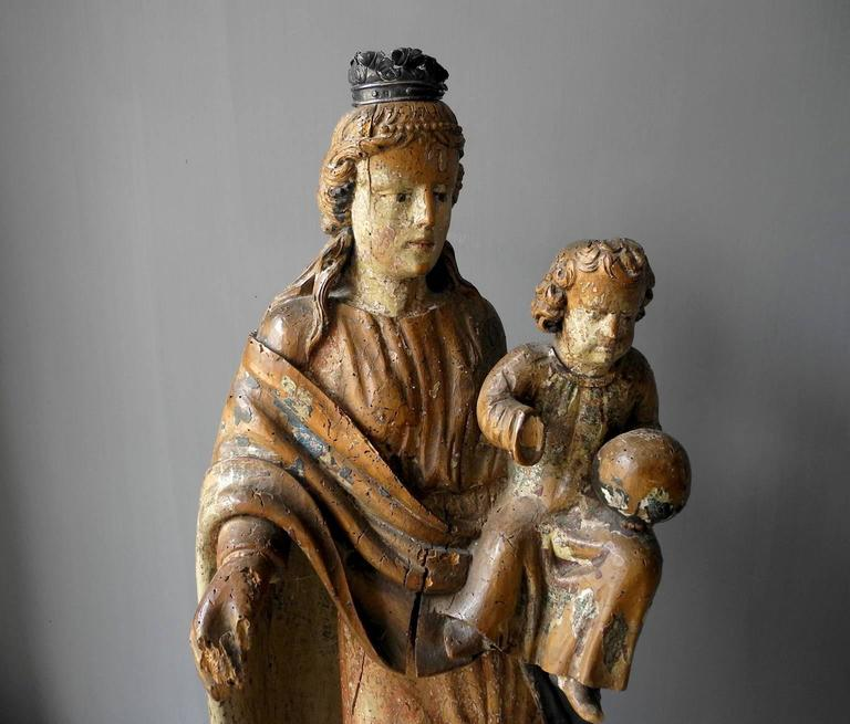 This 17th century painted wooden virgin was found in Italy. It includes its original paint and has somewhat of a patina due to its age. The virgin has a metal crown atop her head and she is holding a baby. It is a perfect size for a historic antique