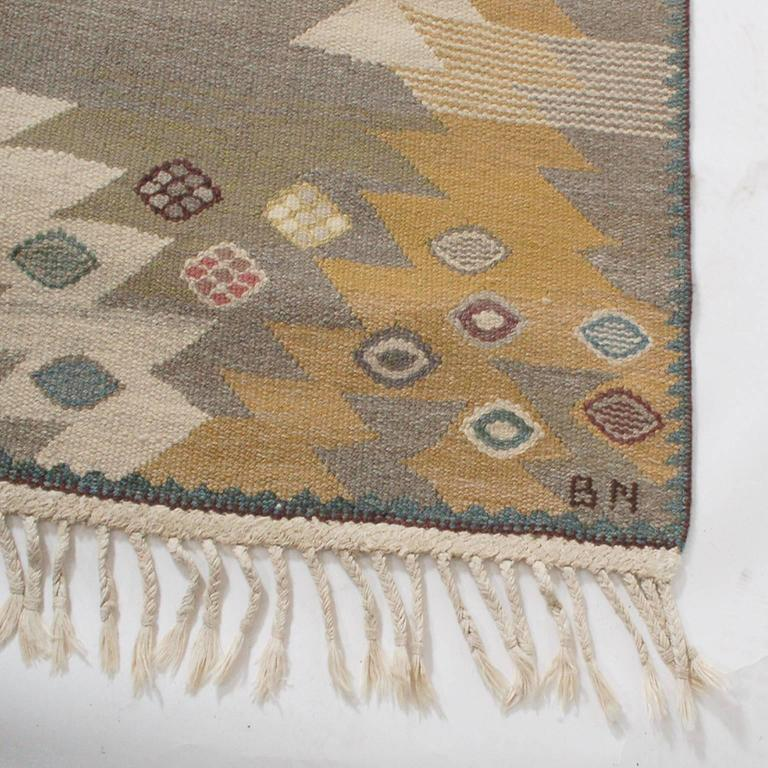 Flat-weave rug created for the Swedish rug company Marta Maas-Fjetterström in the 1950s, by their premiere designer. Retains original fringe. Signed with artist's initials, BN and MMF at the bottom edge.