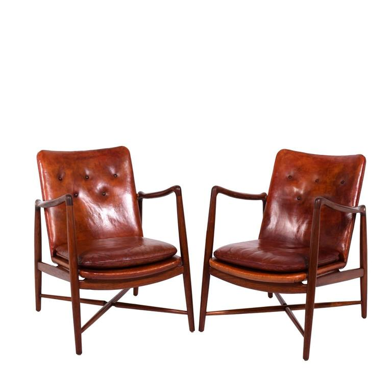 Solid teak frame, organic form arms and X-base stretchers. Upholstered in patinated natural leather with buttoned back. Stamped on bottom, Bo-Ex made in Denmark and retains paper label.