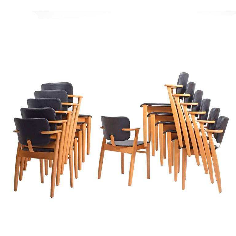 Early production of Ilmari Tapiovaara's most famous armchair designed for the Domus Academica in 1946. Solid birch frame with bent plywood; seat and back upholstered in new black leather. Some with Knoll Associates label and some with finish