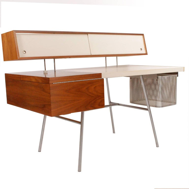 Walnut with original custom white leather writing surface and sliding floating doors, small drawers in maple. Storage and drop down typing table with original perforated aluminum file drawer. On steel legs. Made by Herman Miller.