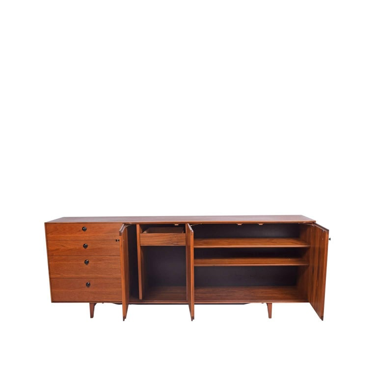 Cabinet features four drawers and three doors concealing two adjustable shelves, one drawer and open storage on solid teak legs with black pulls.