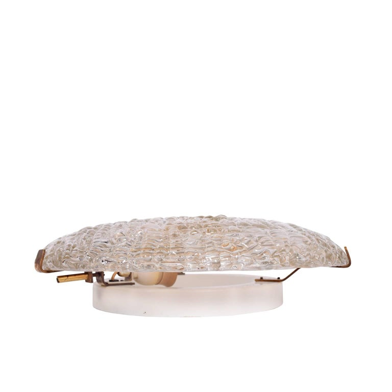 Large round textured glass wall sconce with solid brass holders. Designed by Carl Fagerlund for Orrefors.