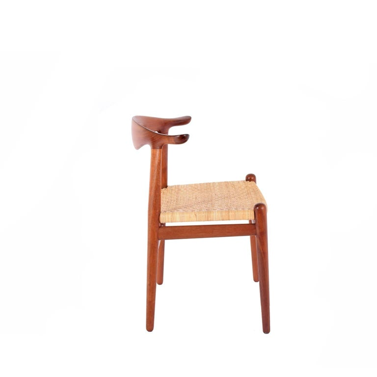Original production Johannes Hansen solid teak cow horn chair with rosewood inlay back and cane seat. Retains labels from cabinet maker.
