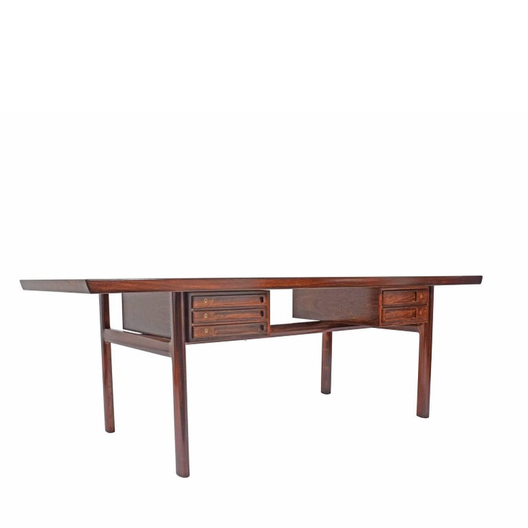 Very functional rosewood desk/table by Peter Hvidt and Orla Mølgaard. Drawer boxes underneath rotate to make more space underneath the top. Label under.