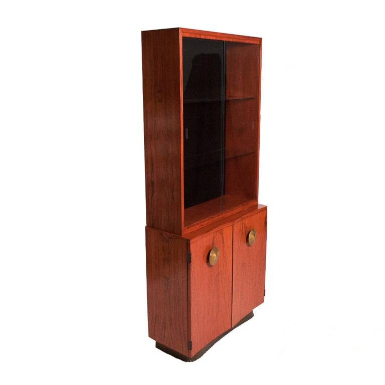 China cabinet with sliding glass doors and two-door cabinet below. Paldao wood cabinets and metal pulls specifically designed for this Paldao group. Cabinet has one wooden shelf, top has two glass shelves. Made by Herman Miller. Design number stamp