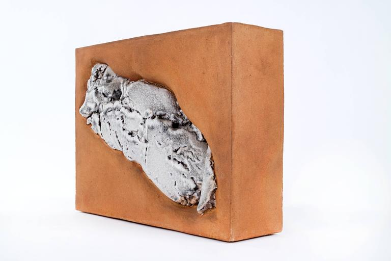 Rectangular block stoneware sculpture with abstract reliefs on both sides.  This item is currently on view in our NYC Greenwich Street Location.
