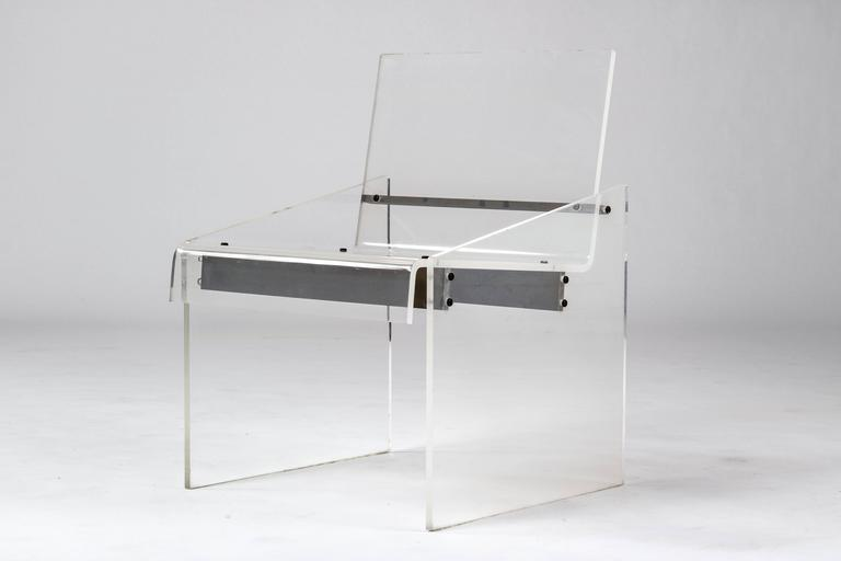 Lucite chair with brass horizontal supports.