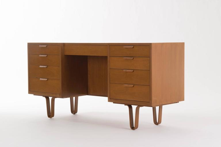 Wormley for Dunbar writing desk. Cherrywood veneer. Features nine drawers with laminated pulls and hairpin legs. Green Dunbar label on inside of drawer.  Measures: Chair clearance: 23.75 in.