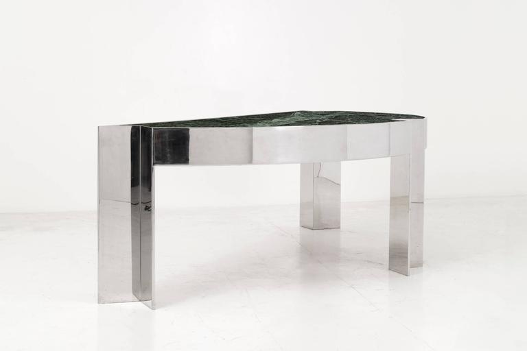 Arced desk with a polished steel frame and verde marble top. Two drawers with laminate fronts and wood inner.  Armchair clearance height: 27 in.