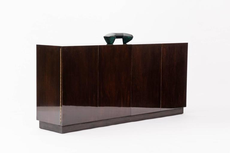Dark brown finished walnut with leather plinth base. Accordion folding doors. 12 pull-out drawers on left and right side, four cubby holes, and one pull-out drawer with felt lining.